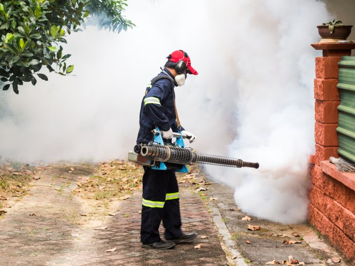 Worker fumigating residential area