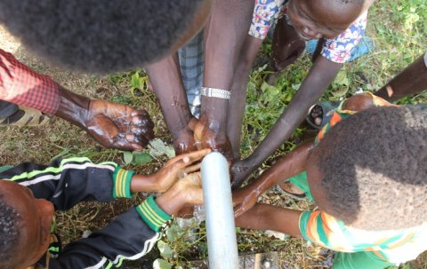 Children celebrate a repaired well as water flows for the first time in years at a healthcare facility (Photo credit: Haik Kocharian for Village Health Partnership)