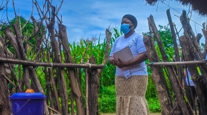 A masked community health worker stands with a notepad at the threshold of a community members gate.